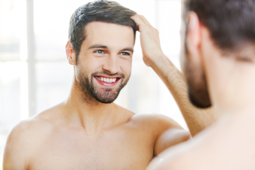 Handsome young man touching his hair with hand and smiling while standing in front of the mirror